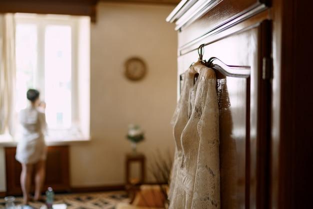 Panna młoda w szlafroku stoi przy oknie w pokoju hotelowym, na drzwiach szafy wisi suknia ślubna