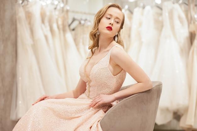 Panna młoda w szykownej sukni pozuje na krześle w ślubnym salonie