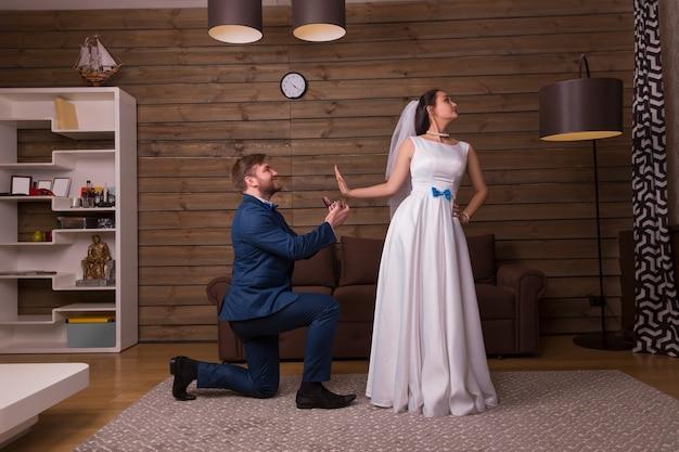 Panna młoda w welonie odrzuca propozycję małżeństwa pana młodego z obrączkami