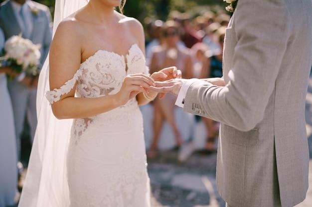Panna młoda wkłada pierścionek na rękę pana młodego
