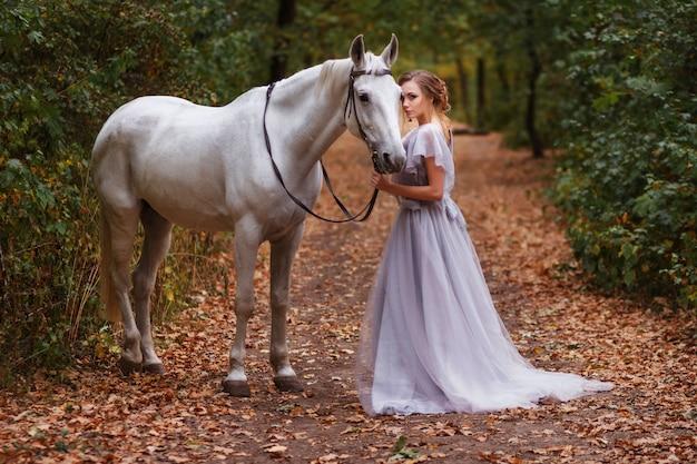 Panna młoda z białym koniem spacery w lesie latem. tło zamazane, efekt artystyczny.