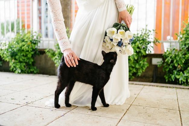 Panna młoda z bukietem ślubnym głaszcząca czarnego kota na ulicy