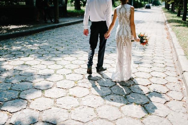 Panna młoda z bukietem ślubnym i pan młody wraca na chodnik