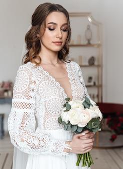 Panna młoda z bukietem świeżych kwiatów w pięknej odświętnej sukience z koronką.
