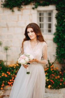 Panna młoda z bukietem w dłoniach stoi pod ścianą domu z zieloną lianą i pomarańczą