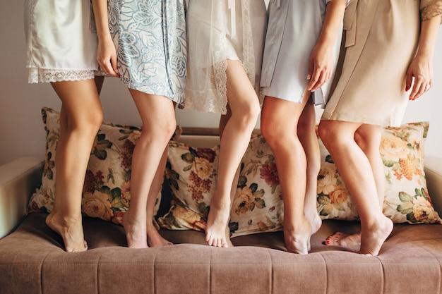Panna młoda z druhenami w szatach na sofie w pokoju hotelowym podczas spotkania przed ceremonią.