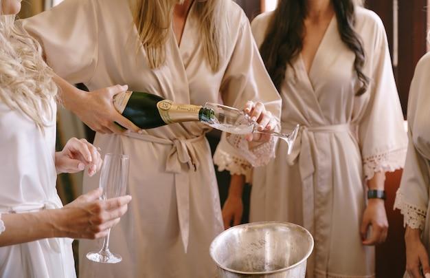 Panna młoda z druhną w szlafrokach nalewa szampana do kieliszków