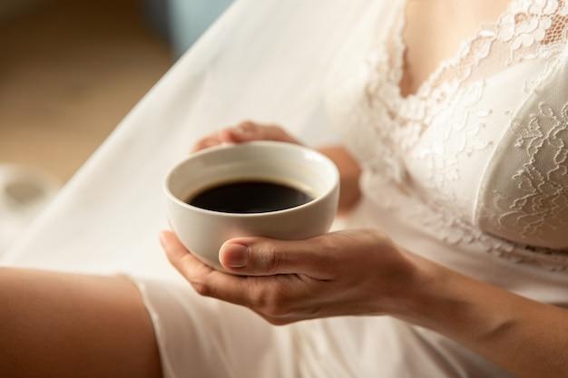 Panna młoda z filiżanką kawy, poranek ślubu, przygotowanie do ślubu