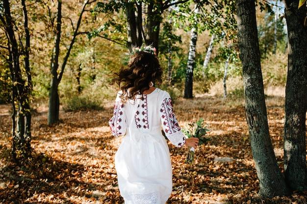 Panna młoda z koroną kwiatów w haftowanej sukience z bukietem biegnie w jesiennym parku.