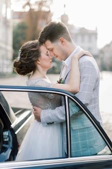 Panna młoda z panem młodym blisko starego samochodu. nowożeńcy całuje i obejmuje podczas gdy stojący za starym czarnym retro samochodem w starym centrum miasta. lwów, ukraina