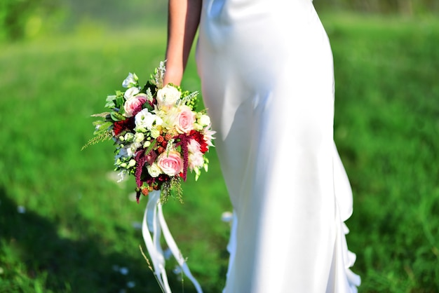 Panna młoda z pięknym bukietem kwiatów na zielonej łące.