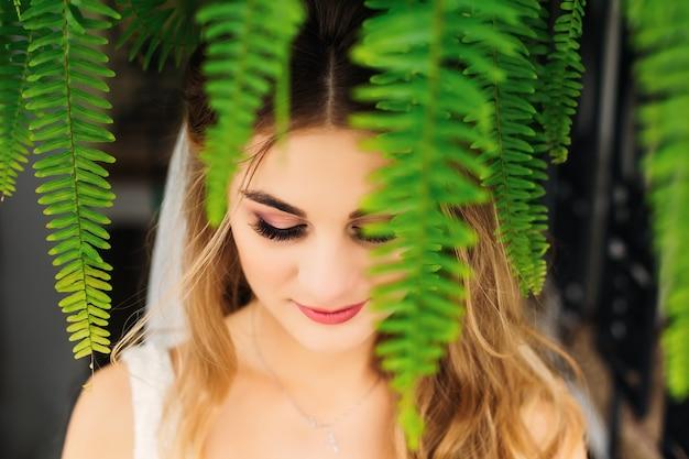 Panna młoda z pięknym makijażem zamknęła oczy, a na pierwszym planie liście paproci z bliska