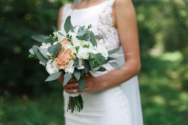 Panna młoda z ślubnym bukietem białych kwiatów na zewnątrz