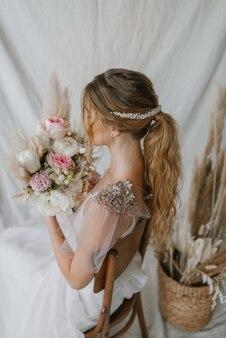 Panna młoda z suknią ślubną i bukietem