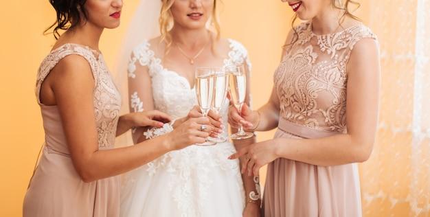 Panna młoda z wesołymi dziewczynami na weselu pije szampana z kieliszków. panna młoda i dziewczyny przytulają się w pokoju. rano panna młoda i dziewczyny.