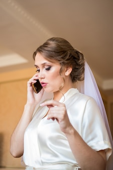 Panna młoda z woalką na głowie rozmawia przez telefon w pokoju hotelowym