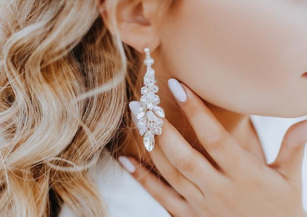Panna młoda zakłada piękne ślubne kolczyki. dziewczyna z fryzurą z lokami nosi biżuterię