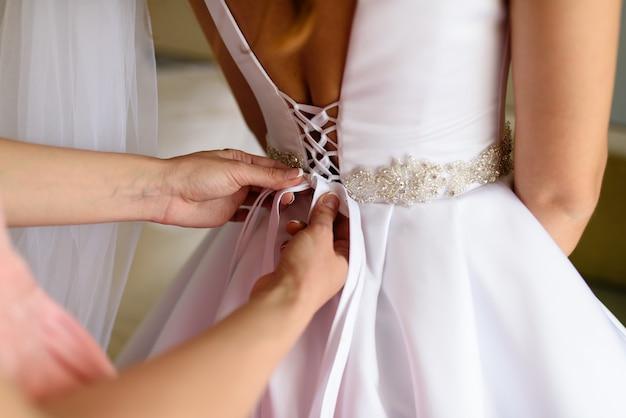 Panna młoda zakładając suknię ślubną
