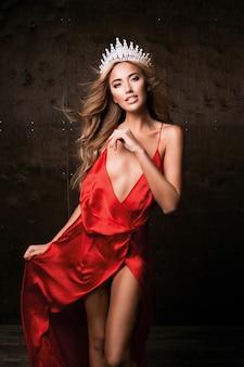 Panna wszechświata ubrana w długą jedwabną czerwoną sukienkę i koronę. naturalny makijaż, kręcona fryzura
