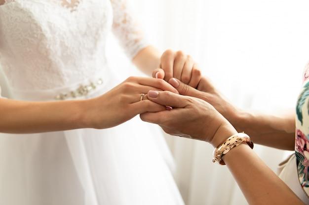 Panny młodej i matki mienia ręki przy dniem ślubu