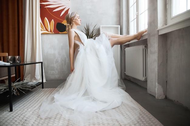 Panny młodej kobieta w lekkiej letniej ślubnej sukni siedzi przy oknie i czeka na ślub