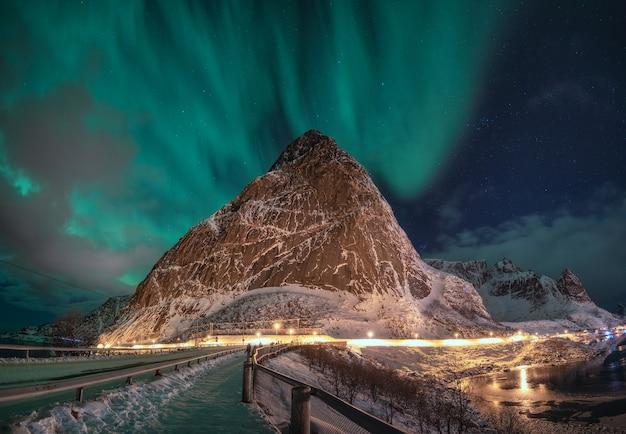 Panorama aurora borealis z gwiazdą nad ośnieżoną górą w reine na lofotach, norwegia