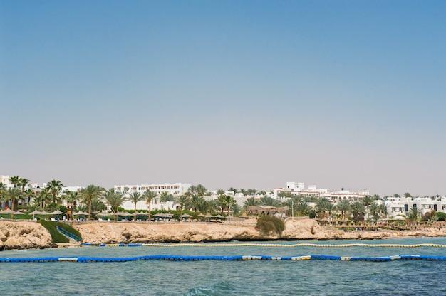 Panorama białego miasta i błękitnego morza z linią brzegową.