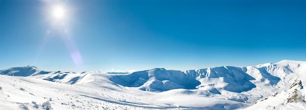 Panorama białych zimowych gór ze śniegiem i jasnym świecącym słońcem i promieniami słonecznymi