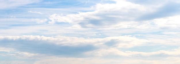 Panorama błękitnego nieba z białymi długimi chmurami w spokojnych pastelowych kolorach