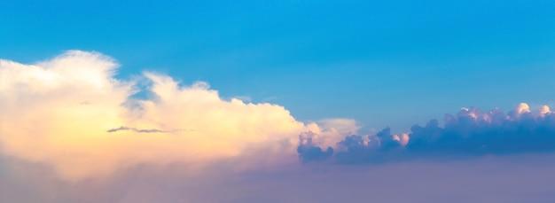 Panorama błękitnego nieba z jasnymi i ciemnymi chmurami o zachodzie słońca