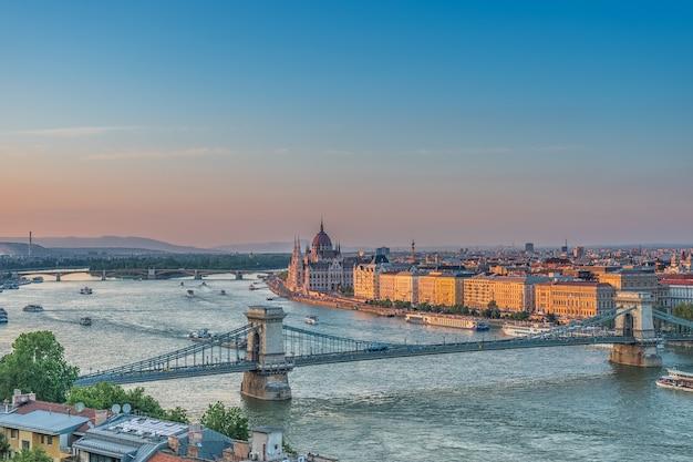 Panorama budapesztu o zachodzie słońca. węgierskie zabytki: most łańcuchowy, parlament i dunaj w budapeszcie.