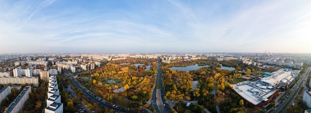 Panorama bukaresztu z drona, park z zielenią i jeziorami, wiele budynków mieszkalnych i handlowych, rumunia