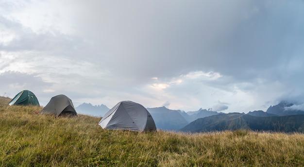 Panorama gór, na polanie są trzy namioty