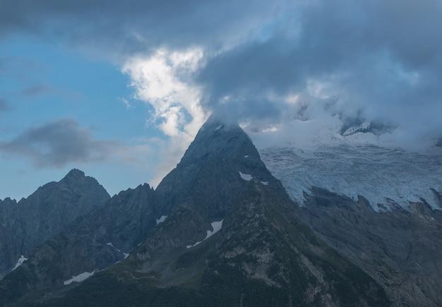 Panorama gór sceny z dramatycznego pochmurnego nieba w parku narodowym dombay, kaukaz, rosja. letni krajobraz i słoneczny dzień
