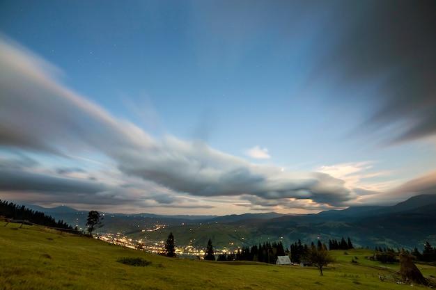 Panorama górska letniej nocy. zielona trawiasta polana górska, świerki na niebieskim tle nieba, kopia przestrzeń tła, jasna droga z jadącymi samochodami i światła mieszkalne poniżej w dolinie.