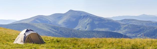 Panorama górska z namiotem turystycznym.