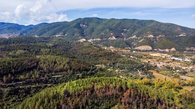 Panorama grecji z drona, kilka zabudowań w dolinie, wzgórza porośnięte bujną zielenią