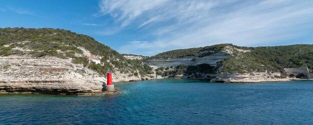 Panorama jachtu do latarni morskiej skały błękitne niebo z małymi chmurami w orientacji poziomej