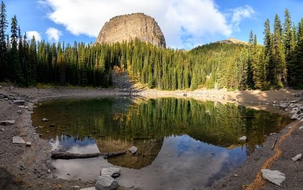 Panorama jeziora lustrzanego z lasem sosnowym odbicie nad stawem w lake louise w parku narodowym banff