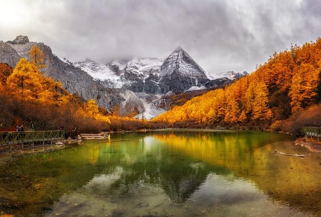 Panorama jeziora perłowego z górą świętego śniegu w sezonie jesiennym w rezerwacie przyrody yading, hrabstwo daocheng, na południowy zachód od prowincji syczuan, chiny. podróż i turystyka, znane miejsce i koncepcja zabytków