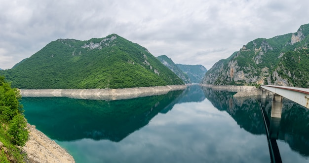 Panorama jeziora piva wśród wysokich malowniczych gór.
