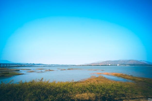Panorama krajobrazu jeziora w tajlandii z koleją po drugiej stronie sceny jeziora i góry na tle przeciw letniemu błękitnemu niebu w prowincji lopburi pa sak jolasid dam