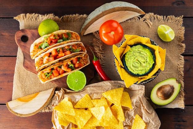 Panorama kuchni meksykańskiej. nachos, guacamole, tacos i składniki na drewnianych deskach. odmiana meksykańskich chipsów taco i nacho tortilla. leżał płasko. widok z góry