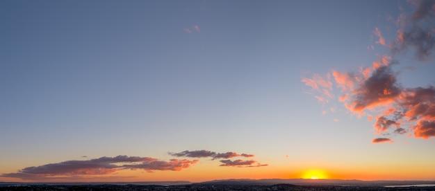 Panorama miasta, ocean i góry o zachodzie słońca.