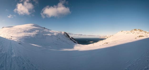 Panorama pasma górskiego śniegu ze słońcem i błękitnym niebem na zimę na lofotach w norwegii