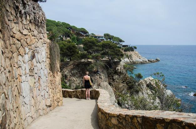 Panorama pięknych skał drogowych w lloret de mar i atrakcyjna młoda kobieta spacerująca w czarnej sukience i żółtej torbie z widokiem na morze. dziewczyna stoi przed toczącym się morzem i skałami w hiszpanii.