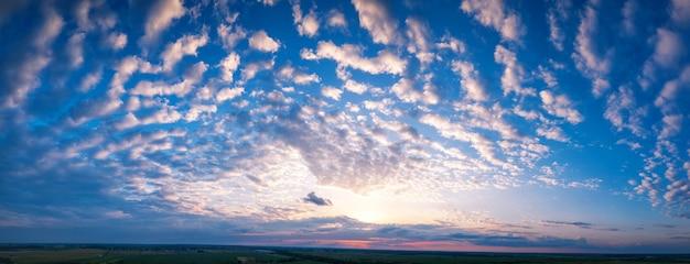 Panorama porannego błękitnego nieba, rozświetlonego pomarańczowym i czerwonym światłem słonecznym, kolorowy świt.