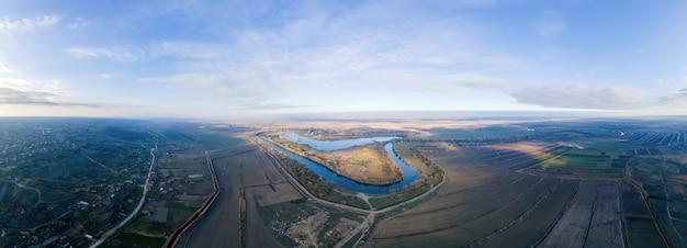 Panorama przyrody w mołdawii. dniestr, wieś z drogami i polami ciągnącymi się po horyzoncie. widok z drona