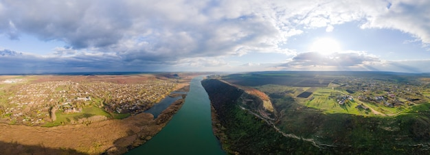 Panorama przyrody w mołdawii. dniestr z dwiema wioskami po bokach rzeki, polami i wzgórzami. widok z drona