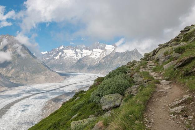 Panorama sceny gór, spacer po wielkim lodowcu aletsch, trasa aletsch panoramaweg w parku narodowym szwajcaria, europa. letni krajobraz, słoneczna pogoda, błękitne niebo i słoneczny dzień